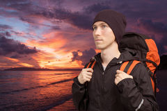 Young man with backpack on the background of sea sunset. Stock Images