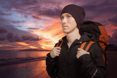 Young man with backpack on the background of sea sunset. Stock Photo