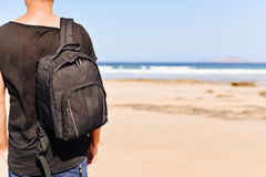 Young man with a backpack on the beach Royalty Free Stock Photography