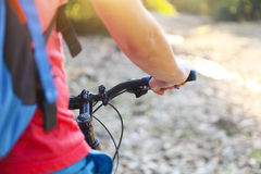Young man with backpack on the bicycle by mountain river. Closeup Stock Images