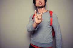 Young man with backpack giving heavy metal gesture Royalty Free Stock Photo