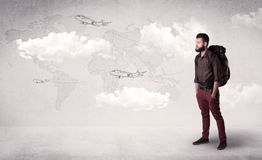 Young man with a backpack. Handsome young man standing with a backpack on his back and planes in front of a world map as a background Royalty Free Stock Photography