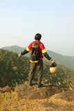 Young man with backpack and helmet standing with raised hands on top of a mountain and enjoying valley view Royalty Free Stock Photography