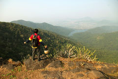 Young man with backpack and helmet standing with raised hands on top of a mountain and enjoying valley view Stock Photo