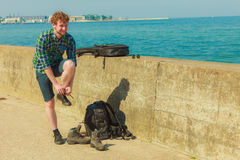 Young man with backpack hikiner on sea coast Stock Photos