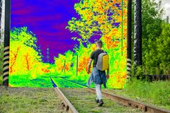 Young man with a backpack on his back goes forward along an abandoned railway to a psychedelic other world. concept of decisive. Young man in jeans and denim stock image