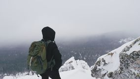 A young man with a backpack on his shoulders, stands on top of a snow-covered mountain and admires the landscape. A young man, a tourist, with a backpack on his stock footage