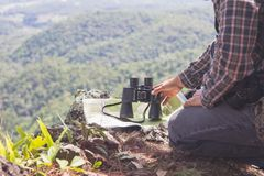 Young man with backpack and holding a binoculars sitting on top of mountain, Hiking and tourism concepts.  royalty free stock photo