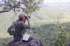 Young man with backpack and holding a binoculars sitting on top of mountain, Hiking and tourism concepts.  stock photos