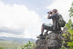 Young man with backpack and holding a binoculars sitting on top of mountain, Hiking and tourism concepts.  stock images