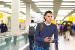 Young man with backpack holding cell phone at Royalty Free Stock Images