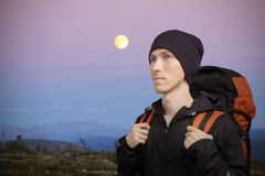 Young man with backpack in mountains. Hilly night landscape with the moon. Young hiker man with backpack in mountains. Hilly night landscape with the moon Stock Image