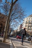 Young man with backpack rides an electric push scooter on the road, Barcelona, Spain stock image