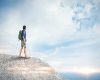Young man with backpack on the rock. Visual royalty free stock photography