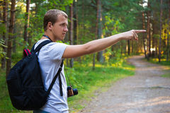 Young man with backpack showing on something in forest Royalty Free Stock Photos