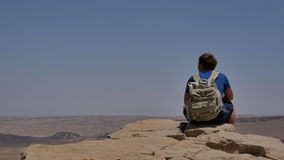 Young man with backpack sitting on cliff`s edge and enjoying the desert view stock video