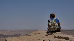 Young man with backpack sitting on cliff`s edge and looking at the desert stock video footage