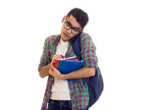 Young man with backpack, smartphone and books. Young attractive man with black hair in white T-shirt and checkered shirt with blue backpack holding books and Royalty Free Stock Photo