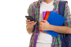 Young man with backpack, smartphone and books. Young man with black hair in white T-shirt and checkered shirt with blue backpack holding books and using Royalty Free Stock Image