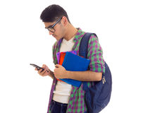 Young man with backpack, smartphone and books. Young handsome man with black hair in white T-shirt and checkered shirt with blue backpack holding books and using Stock Image