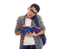Young man with backpack, smartphone and books. Handsome young man with black hair in white T-shirt and checkered shirt with blue backpack holding books and using Stock Photography