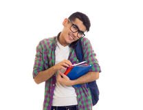 Young man with backpack, smartphone and books. Young happy man with black hair in white T-shirt and checkered shirt with blue backpack holding books and using Royalty Free Stock Images