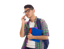 Young man with backpack, smartphone and books. Young nice man with black hair in white T-shirt and checkered shirt with blue backpack holding books and using Royalty Free Stock Image