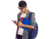 Young man with backpack, smartphone and books. Young optimistic man with black hair in white T-shirt and checkered shirt with blue backpack holding books and Stock Images