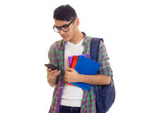 Young man with backpack, smartphone and books. Young pleasant man with black hair in white T-shirt and checkered shirt with blue backpack holding books and using Royalty Free Stock Photography