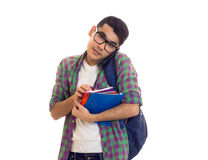 Young man with backpack, smartphone and books. Young positive man with black hair in white T-shirt and checkered shirt with blue backpack holding books and using Stock Photo