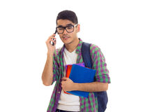 Young man with backpack, smartphone and books. Young smart-looking man with black hair in white T-shirt and checkered shirt with blue backpack holding books and Royalty Free Stock Image