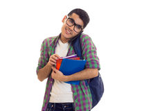 Young man with backpack, smartphone and books. Smiling young man with black hair in white T-shirt and checkered shirt with blue backpack holding books and using Stock Image