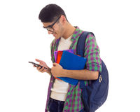 Young man with backpack, smartphone and books. Young smiling man with black hair in white T-shirt and checkered shirt with blue backpack holding books and using Royalty Free Stock Image