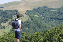 Young man with backpack standing on cliff's edge and looking to Stock Photos