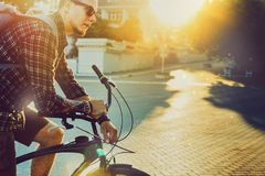 Young Man Cyclist With Bicycle Daily Routine Lifestyle Toned. Young Man With Backpack And Sunglasses Sits On Bicycle Against Bright Morning Sun royalty free stock images