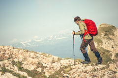 Young Man with backpack and trekking poles running outdoor. Travel Lifestyle hiking concept rocky mountains on background Summer vacations Royalty Free Stock Image