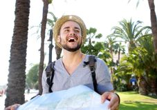 Young man with backpack on vacation laughing with map Royalty Free Stock Image