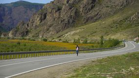 Young traveler man with backpack walking alone on the road on the mountain. Hitchhiker on a road. Travel. 4 k. Young man with backpack walking alone on the road stock footage