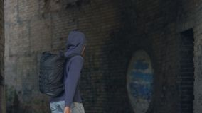 Young man with backpack walking outdoors abandoned building leaving city despair. Stock footage stock footage