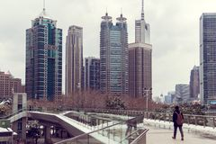 A young man with a backpack is walking on a pedestrian crossing against the backdrop of skyscrapers of Shanghai, China Stock Photography