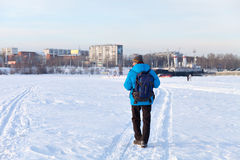 Young man with backpack walking on snow cover.  his back to the camera. Leaving footprints in the . Stock Images