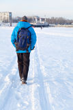 Young man with backpack walking on snow cover.  his back to the camera. Leaving footprints in the . Stock Photography