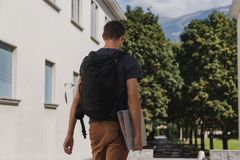 Young man with backpack walking to school after summer holidays stock image