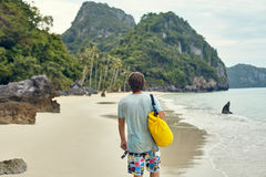 Young man with backpack walking on tropical beach Royalty Free Stock Image