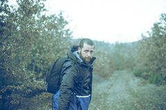 Young man backpacker on a forest road Royalty Free Stock Photography