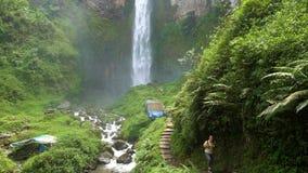 Young man backpacker walking towards beautiful Sipiso-Piso waterfall stock video