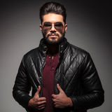 Young man with a bad boy look. Wearing leather jacket and sunglasses, on gray background stock image