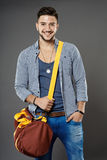 Young man with bag. Fashionable young man with bag on gray background stock photo