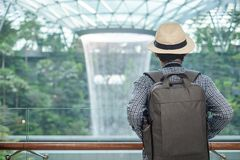 Young man with bag and hat, Asian traveler standing and looking to beautiful rain vortex at Jewel Changi Airport, landmark and. Popular for tourist attractions royalty free stock photography