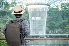 Young man with bag and hat, Asian traveler standing and looking to beautiful rain vortex at Jewel Changi Airport, landmark and. Popular for tourist attractions stock image
